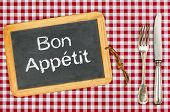 Blackboard with the text Bon Appetit on a checkered tablecloth