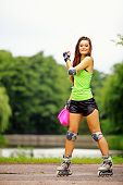 foto of roller-skating  - Happy young girl enjoying roller skating rollerblading on inline skates sport in park - JPG
