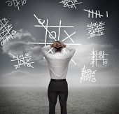 Anxious businessman losing at noughts and crosses with hands on head