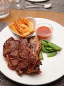 T-bone steak with french fries and hot sauce in plate