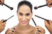 Beautiful woman encircled by make up brushes on white background