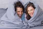 Smiling couple having fun wrapped in their duvet at home