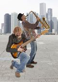 The duo of musicians with guitar and saxophone against the background of skyscraper
