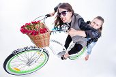 Two Girls Riding A Bike Making Funny Faces - Isolated On Bluish Background