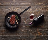 Beef steak in a grill pan with wine bottle and wine glass on old wood background. Juicy food background.