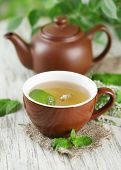 pic of teapot  - Teapot and cup of herbal tea with fresh mint flowers on wooden table - JPG