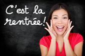 C'est la Rentree Scolaire - French student screaming happy Back to School written in French on blackboard by woman teacher. Smiling happy female teaching French language or university college student