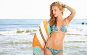 Beautiful sexy young woman surfer girl in bikini with surfboard at a beach