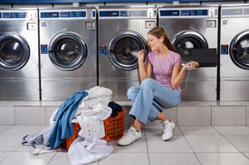 pic of laundromat  - Young woman with laundry basket enjoying music while sitting at laundromat - JPG