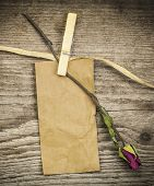 Paper note with dried rose on a old wooden boards