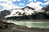 stock photo of low-light  - Low clouds above Tasman glacier lake in New Zealand - JPG