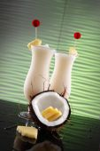 stock photo of pina-colada  - Pina colada or coco cream smoothies wedged with a pineapple slice on a wavy mint background - JPG