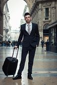 Portrait Of A Handsome Young Businessman With Wheeled Suitcase