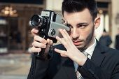 Handsome Young Businessman Using A Vintage Film Camera