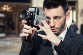 Handsome Young Businessman Using A Vintage Film Camera