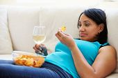 Overweight Woman At Home Eating Chips And Drinking Wine