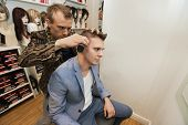 Barber shaving male customer's hair in shop