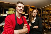 Portrait of confident store clerks in cheese shop