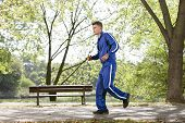Full length side view of man jogging on path in park