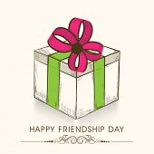 Beautiful gift box wrapped in green and pink ribbon on beige background for Happy Friendship Day celebrations.