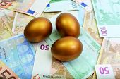 foto of laying eggs  - Three Golden Eggs laying on a bed of money - JPG