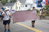 Men carry sign in the Wellfleet 4th of July Parade in Wellfleet, Massachusetts.