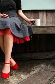 50s girl in red shoes drinking coffee