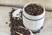 Scattered Roasted Coffee Beans Around A Wooden Barrel