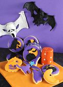 stock photo of ghoul  - Happy Halloween party trick or treat purple and orange cookies with pumpkins cats ghost moon and witches hat with ghoul and bat decorations - JPG