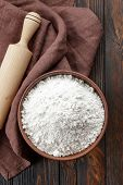 stock photo of cereal bowl  - White flour in a bowl on a wooden table - JPG
