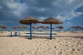 Different Parasols And Sun Loungers On The Empty Beach On Tavira Island, Algarve. Portugal