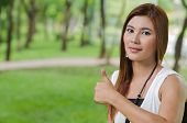 Attractive young Asian woman giving a thumbs up