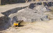 stock photo of power-shovel  - yellow excavator machine stonecutter rubble near the rocks in a quarry for the extraction of granite