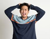 Portrait Of Mad Asian Man Pulling His Hair On Plain Background