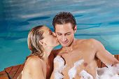 Happy woman kissing man in whirlpool in spa in their holidays