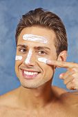 Happy young man treating his face with skin lotion