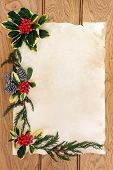 Winter and christmas background floral border with holly, cedar leaf sprigs and pine cones over old