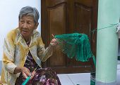 Old Lady Weaves Fishing Net In Front Of Her Home.