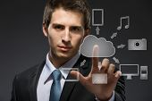 Young businessman working with cloud technology on black background