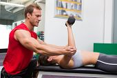 Personal trainer helping client lift dumbbells at the gym
