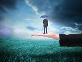 Businessman holding umbrella against blue sky over green field
