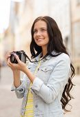 tourism, travel, leisure, holidays and friendship concept - smiling teenage girl with camera taking