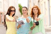 tourism, travel, leisure, holidays and friendship concept - smiling teenage girls with city guide an