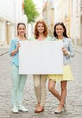 vacation, advertising and friendship concept - smiling teenage girls holding white blank billboard on city street