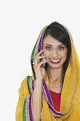 stock photo of salwar  - Portrait of Indian woman in traditional wear attending phone call over gray background - JPG