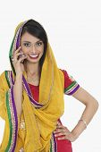 stock photo of dupatta  - Portrait of an Indian woman in traditional wear answering phone call over gray background - JPG