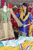 stock photo of dupatta  - Portrait of Indian designer measuring traditional outfit at design studio - JPG
