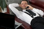 Businessman Laying On Couch With A Phone