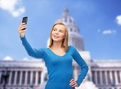 technology, travel and internet concept - smiling woman taking self picture with smartphone camera