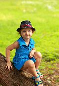 Funny Fashion Kid Girl In Blue Bright Dress Sitting On Tree On Summer Green Background